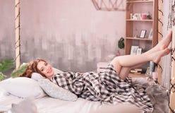 Рыжеволосая беременная женщина лежит в уютной кровати стоковые фотографии rf