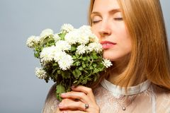 Рыжеволосая девушка в студии с белым букетом цветков стоковая фотография