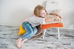Рыжеволосая девушка сидя на подушках Стоковое фото RF