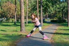 Рыжеволосая девушка с оплетками катается на коньках на розовых роликах и падается внутри стоковое изображение