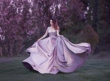 Рыжеволосая девушка танцует и закручивает в роскошное, достойный, сирень, фиолетовое платье Ткань красиво летает внутри стоковое фото rf
