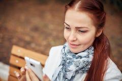 Рыжеволосая средн-постаретая женщина с smartphone в ее руке сидит на стенде в парке и связывает в социальных сетях стоковое фото rf