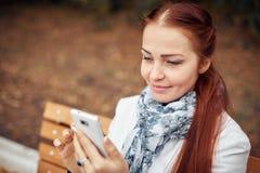 Рыжеволосая средн-постаретая женщина с smartphone в ее руке сидит на стенде в парке и связывает в социальных сетях стоковые изображения