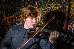 Рыжеволосый freckled мальчик играя скрипку с различными эмоциями o стоковые фотографии rf