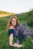 Рыжеволосая девушка в голубом платье с lupines Стоковое Фото