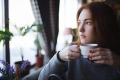 Рыжеволосая девушка в кофе свитера выпивая стоковое фото rf