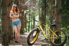 Рыжеволосая девушка в шортах стоит рядом с желтым fatbike велосипеда Стоковая Фотография