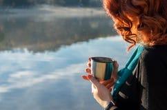рыжеволосая девушка держа в ее руках чашка от thermos Стоковые Изображения