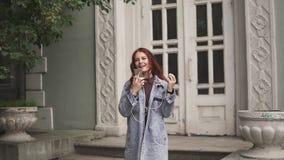 Рыжеволосая девушка носит наушники и слушает к музыке от мобильного телефона подросток в наушниках на предпосылке города видеоматериал