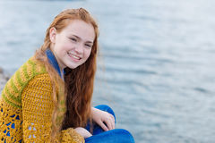Рыжеволосая девушка при веснушки сидя на seashore Стоковая Фотография