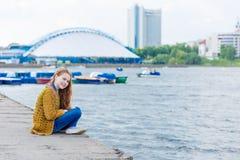 Рыжеволосая девушка при веснушки сидя на seashore Стоковое фото RF