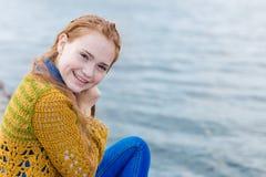 Рыжеволосая девушка при веснушки сидя на seashore Стоковая Фотография RF