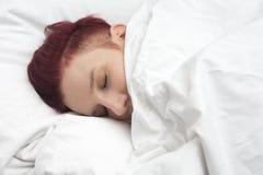 Рыжеволосая женщина спать в кровати стоковые фото
