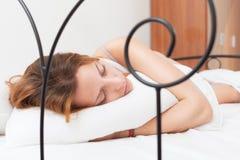 Рыжеволосая женщина спать на белой подушке в кровати Стоковые Изображения