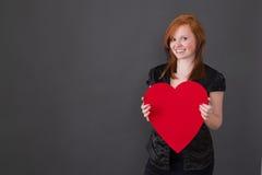 Рыжеволосая женщина с сердцем в руке стоковое изображение rf
