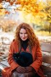 Рыжеволосая усмехаясь красивая женщина с черным котом Стоковая Фотография RF