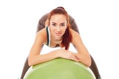 Рыжеволосая sporty девушка представляя с шариком фитнеса Стоковое Изображение RF