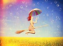 Рыжеволосое летание девушки с зонтиком Стоковые Изображения