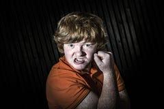 Рыжеволосый мальчик показывая бицепс с угрожает стороны стоковые фотографии rf