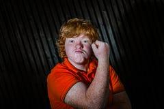 Рыжеволосый мальчик показывая бицепс с угрожает стороны стоковое изображение rf