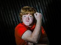 Рыжеволосый мальчик показывая бицепс с угрожает стороны стоковая фотография