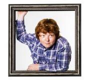 Рыжеволосый мальчик представляя с картинной рамкой стоковая фотография