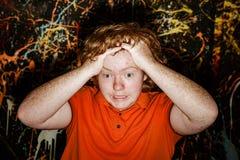 Рыжеволосый мальчик принимая его головную показывая ситуацию катастрофы стоковая фотография