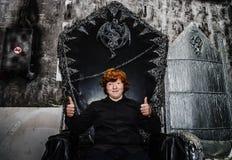 Рыжеволосый мальчик сидя на волшебном троне стоковое изображение rf