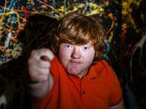 Рыжеволосый смешной мальчик показывая знак смоквы стоковая фотография
