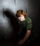 Рыжеволосый freckled тучный мальчик представляя как солдат стоковое изображение