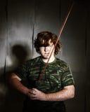 Рыжеволосый freckled тучный мальчик представляя как солдат стоковые фотографии rf
