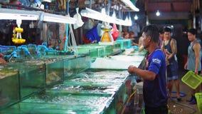 Рынок ночи морепродуктов в Азии, крабах и омарах в аквариумах для продажи к ресторанам и туристам акции видеоматериалы