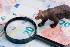 Рынок с понижательной тенденцией в концепции финансовых и вклада, диаграмме гризли идя на деньгах банкнот евро с лупой, brexit стоковые изображения rf