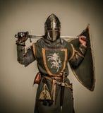 Рыцарь держа шпагу за его назад Стоковые Изображения