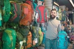 Рюкзаки клиента молодого человека рассматривая в магазине Стоковая Фотография RF