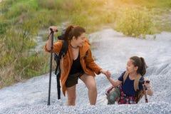 Рюкзаки перемещения мамы и ребенк стоя в горе для природы образования стоковое изображение rf
