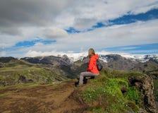 Рюкзак активной молодой женщины hiker небольшой сидя наслаждающся ландшафтом вулкана с долиной гор ледника зеленой и снегом Thors стоковое фото rf