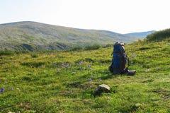 Рюкзак на луге травы с горами на предпосылке Лето мотивационное изобр стоковые изображения rf