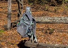 Рюкзак ` s hiker полагается вверх против старой загородки разделенного рельса Стоковые Изображения