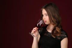 Рюмка девушки касающая ее губами конец вверх темнота предпосылки - красный цвет Стоковая Фотография RF