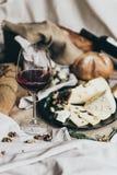 Рюмка заполнена при сухое красное вино лежа позади Свежий хлеб, голубой сыр, сыр masdaam, яичка триперсток и гайки стоковая фотография