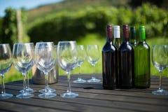 Рюмки и бутылки на таблице Стоковое Фото