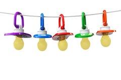 Рядок pacifiers младенцев с веревочкой Стоковые Фотографии RF