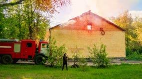 Рядом с пожарной машиной девушка сфотографировала на доме smartphone покинутом горением стоковые фотографии rf