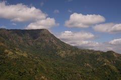 Ряд зеленой горы под пасмурным голубым небом стоковое фото rf