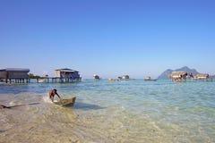 САБАХ, МАЛАЙЗИЯ - 19-ОЕ АПРЕЛЯ: Неопознанные дети Bajau Laut на шлюпке Стоковая Фотография RF