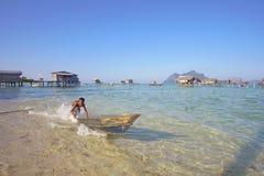 САБАХ, МАЛАЙЗИЯ - 19-ОЕ АПРЕЛЯ: Неопознанные дети Bajau Laut на шлюпке Стоковое Изображение