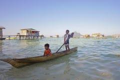 САБАХ, МАЛАЙЗИЯ - 19-ОЕ АПРЕЛЯ: Неопознанные дети Bajau Laut на шлюпке Стоковая Фотография
