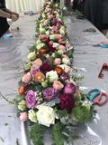 Садовник аранжируя цветки на обеденном столе стоковые изображения rf