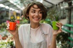 Садовник женщины стоя над заводами цветков в парнике держа заводы стоковые фотографии rf